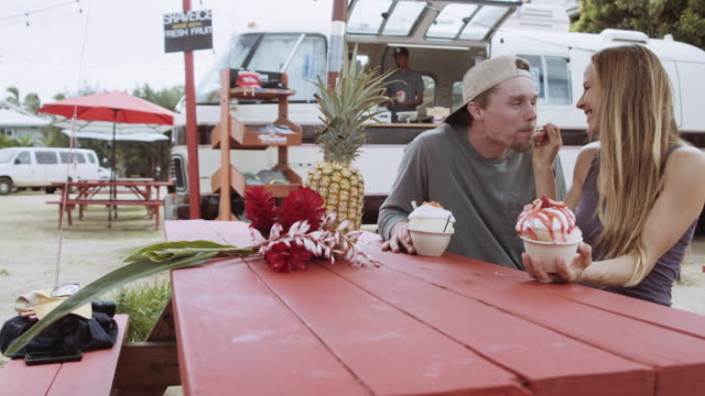 Attractive couple eating shaved ice Attractive couple eating shaved ice small business saturday stock videos & royalty-free footage