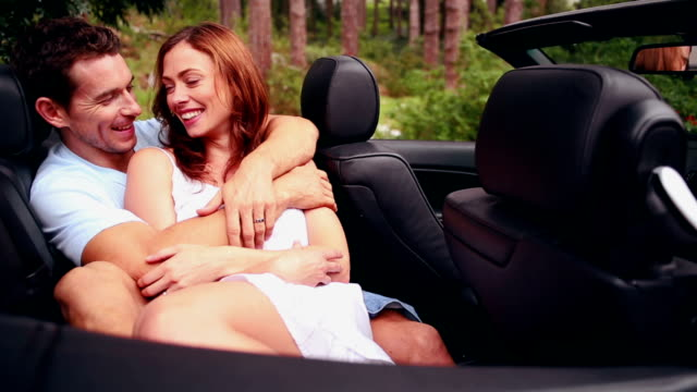 Attractive couple embracing in a convertible car