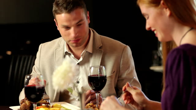 Attractive couple having dinner together video