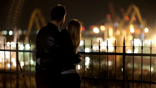 attractive couple in love embrace and enjoy an intimate moment together at night, against the backdrop of port lights - date night stock videos & royalty-free footage