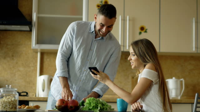 Attractive couple in the kitchen early morning. Beautiful girl sharing social media on smartphone with her boyfriend video