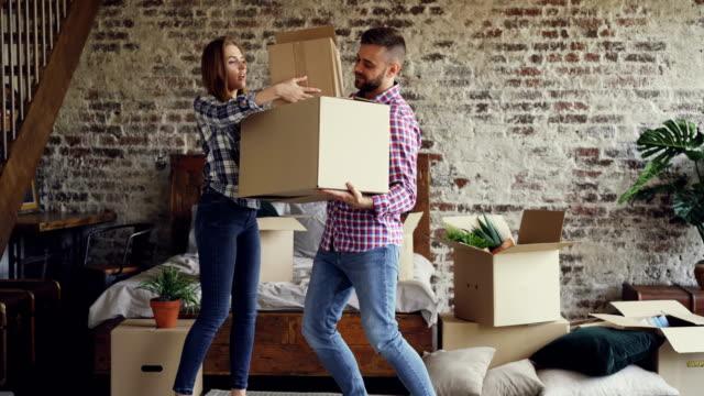 Couple attrayant se déplace de boîtes dans la chambre à coucher dans leur nouvelle maison, guy mène les choses tandis que sa copine lui aide. Concept de personnes et le déplacement. - Vidéo