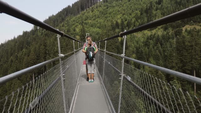 Attractive couple kissing on a suspension bridge in the mountains. Attractive couple kissing on a suspension bridge in the mountains. Walk outdoors. Beautiful landscape in the Alps. suspension bridge stock videos & royalty-free footage