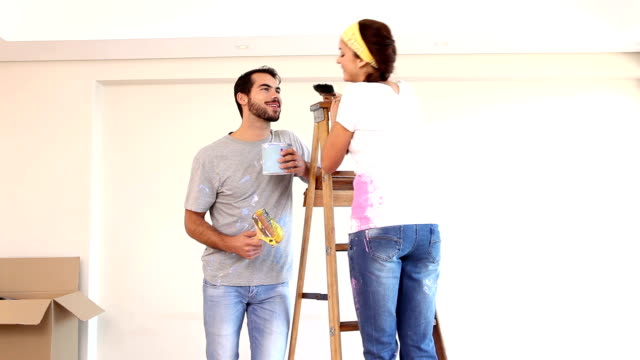 Attractive couple painting their living room video