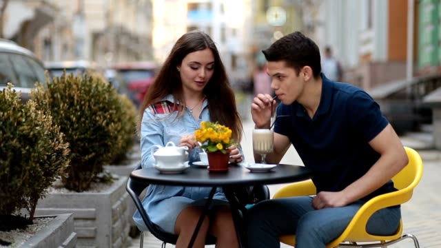 Attractive couple relaxing in sidewalk cafe video