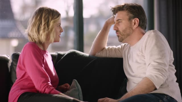 attractive couple sitting on sofa and talking seriously - relazione umana video stock e b–roll