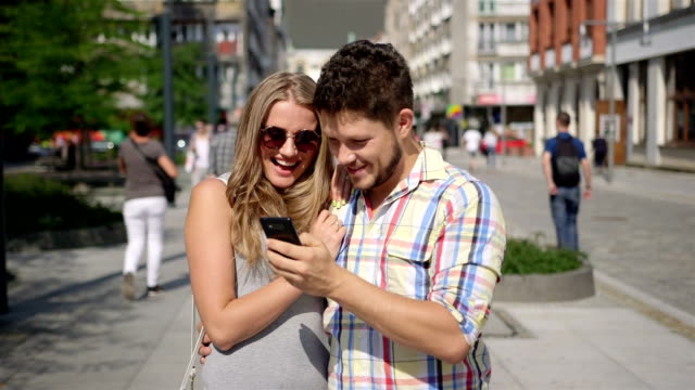 Attractive couple taking self-portrait with smartphone in a city street video
