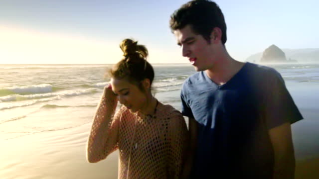 Attractive couple walk on beach together video