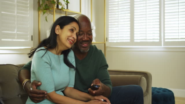 Attractive Couple Watching Television at Home An Indian woman and Afro-Latino man in their 50s are relaxing on the couch in their lovely home, embracing as they watch something on television. 50 54 years stock videos & royalty-free footage
