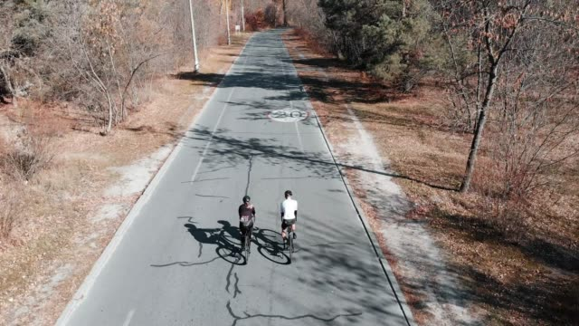 Attractive cycling couple is riding on road bikes in empty autumn park with fallen leaves. Back follow drone view of male and female cyclists training on bicycles at sunny warm day