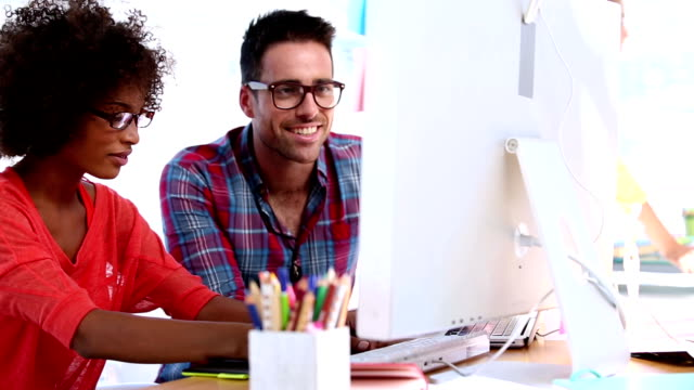 Attractive designers working together on a computer video