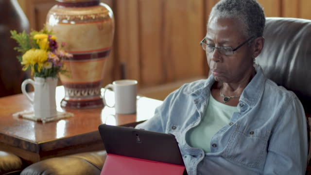Attractive elderly black woman using a digital tablet in her living room - dolly