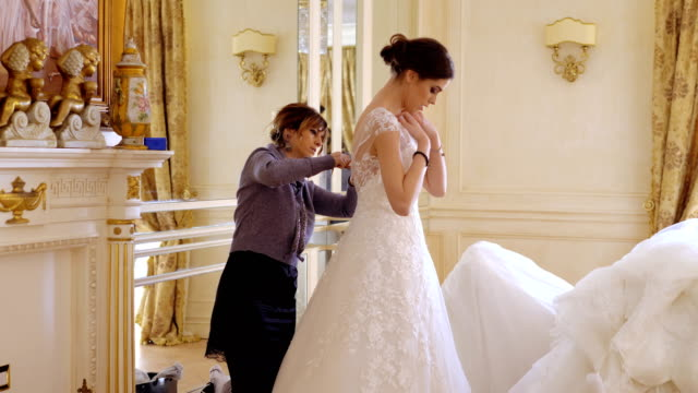 attractive elegant bride is helped  by seamstress into her wedding dress. - alta moda italy video stock e b–roll