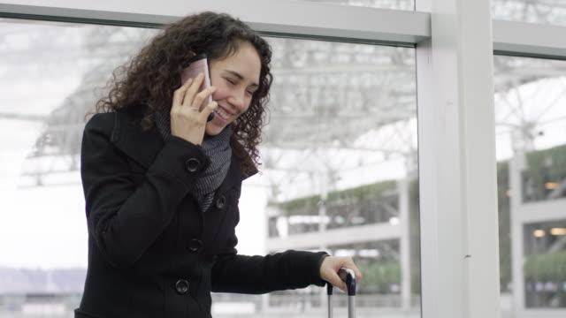 Attrayante femme ethnique chatter sur un téléphone cellulaire pendant qu'il attend avec sa valise - Vidéo