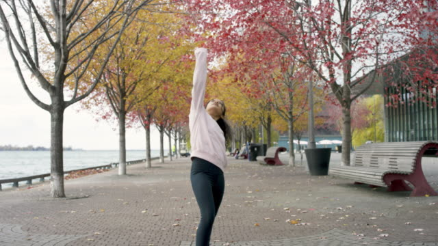 Attractive ethnic young adult female doing yoga outside during fall video