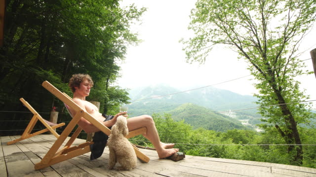 attraktiven fairhaarigen kerl mit einem glas bier schaut auf streunenden hund - sun chair stock-videos und b-roll-filmmaterial