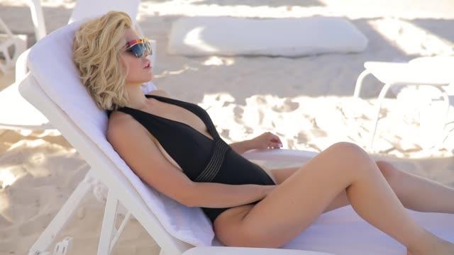 attractive fashion woman in bikini lying on a chaise-longue, turn face - bikini video stock e b–roll
