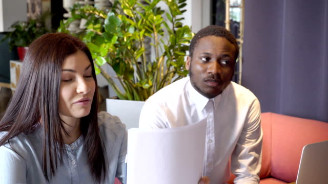 Attractive female and African guy are sitting at informal meeting in restaurant