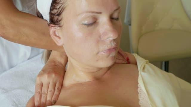 vidéos et rushes de femme séduisante spa health club recevant un massage du visage - allongé sur le dos