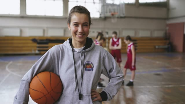 Attractive female basketball coach Young beautiful female basketball coach standing in school gym , holding basketball ball , looking at camera and smiling coach stock videos & royalty-free footage