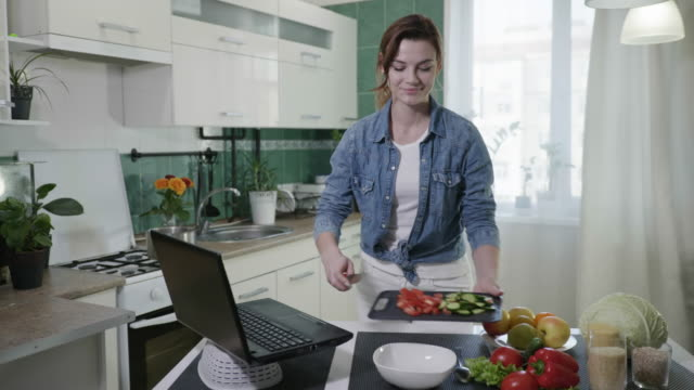 attraktive weibliche hausfrau auf diät zubereiten vegetarischen salat von frischem gemüse nach video-rezept aus beliebten blog über gesunde ernährung beim stehen am tisch in - bloggen stock-videos und b-roll-filmmaterial
