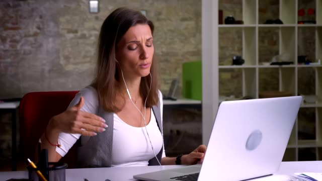 Attractive female office worker in earphones having a conversation on her laptop on the workplace indoors Attractive female office worker in earphones having a conversation on her laptop on the workplace indoors. online meeting stock videos & royalty-free footage