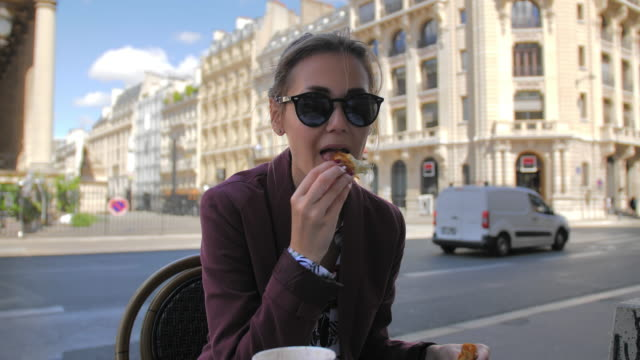 attractive female parisian eating a croissant in a street cafe in the center of paris. against the background of a typical french cityscape. slow motion, france - francuska kuchnia filmów i materiałów b-roll