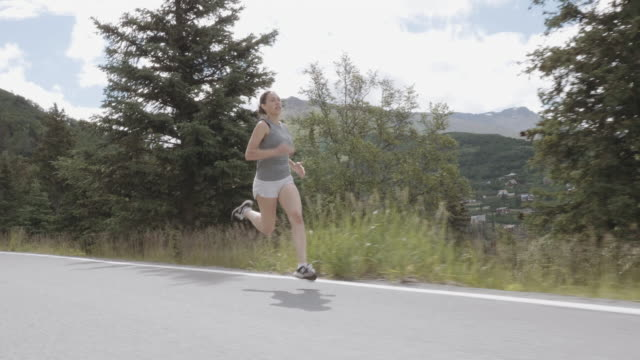 UHD 4K SLOMO: Attractive female runner on a scenic highway in the mountains video