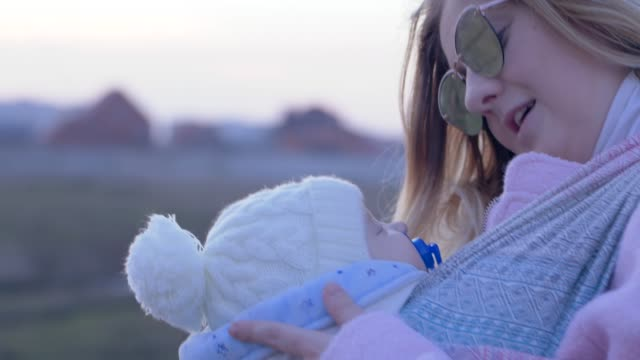 attractive female with newborn in sling while walking in open air close-up - ciuccio video stock e b–roll