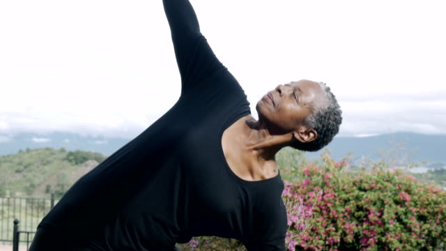 Attractive fit African American woman in 60s practicing yoga triangle pose