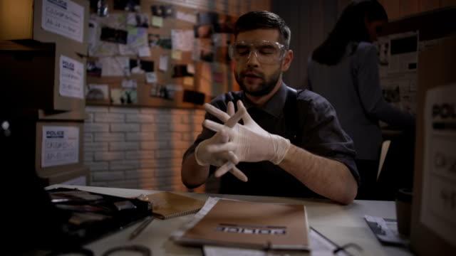 привлекательный судебно-медицинский эксперт, работающий с вещественными доказательствами в отделе полиции - expert стоковые видео и кадры b-roll