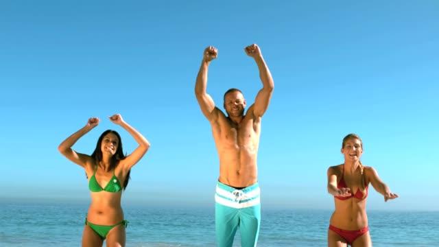 매력적인 프렌즈 뛰어내림 해변 동시에 - 20 29세 스톡 비디오 및 b-롤 화면