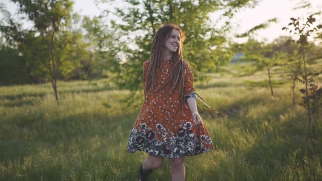 attractive fun hippie woman with dreadlocks in the woods at sunset having good time outdoors video