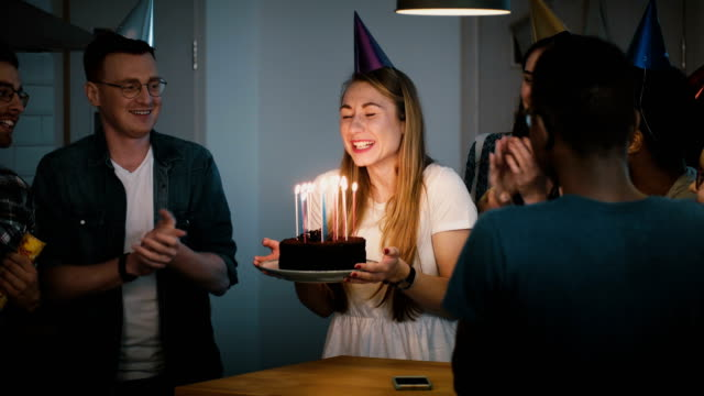 Attractive girl blows on birthday cake candles. Making a wish. Diverse multi ethnic group celebrate together. Festive 4K video