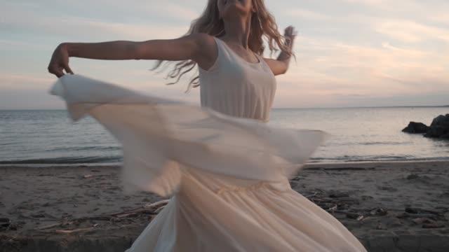 vídeos de stock e filmes b-roll de attractive girl dancing on the beach in a fluttering dress. - tule têxtil
