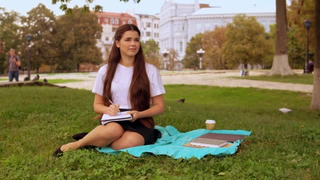 vídeos de stock e filmes b-roll de attractive girl doing homework outdoors - saia