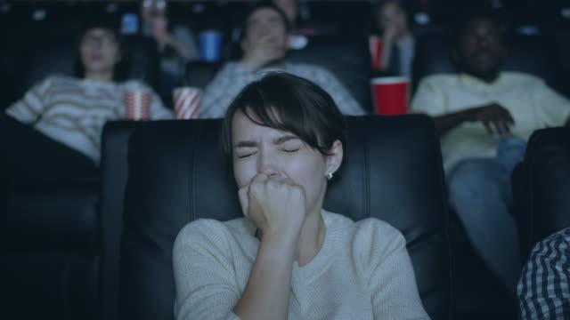 attractive girl feeling scared during horror film in dark modern cinema - donna si nasconde video stock e b–roll