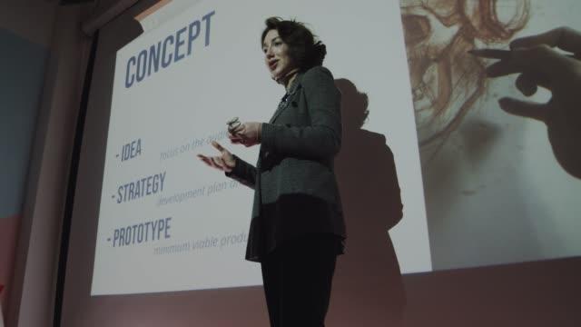 attraktiv flicka ger en presentation till publiken - diabild bildbanksvideor och videomaterial från bakom kulisserna