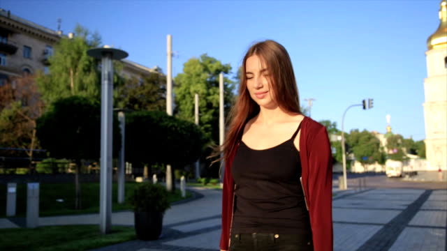 attractive girl in a red coat with red lips goes by the street in a city than turns to camera and smiles - rossetto rosso video stock e b–roll