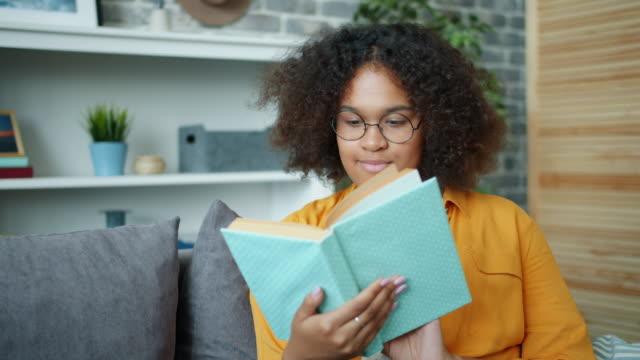 stockvideo's en b-roll-footage met aantrekkelijk meisje in glazen lezen boek en glimlachend zittend op de bank in appartement - literatuur