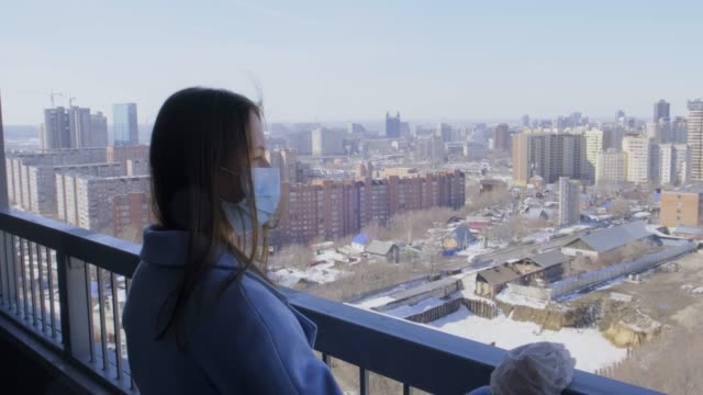 vídeos de stock e filmes b-roll de attractive girl in turquoise coat, stands on balcony in protective gloves and medical mask, girl observes precautions for spread of coronavirus, safety first, pandemic prevention, covid-19, loneliness - covid hair