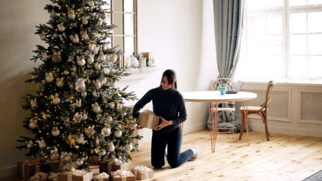 attractive girl is bringing gift boxes to christmas tree, putting them under fir-tree and smiling then touching beautiful decorations. holidays and presents concept. - decorare video stock e b–roll