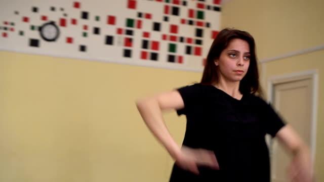 vidéos et rushes de jolie jeune fille effectue une danse moderne dans un studio de danse. coup de grue - justaucorps