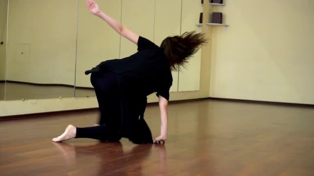 attraktive mädchen führt einen modernen tanz in einem tanzstudio. kran-shot - gymnastikanzug stock-videos und b-roll-filmmaterial