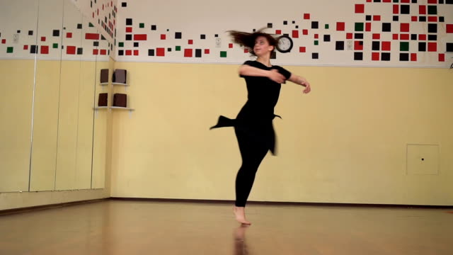 Attractive girl performs a modern dance in a dance studio. Crane shot Attractive girl performs a modern dance in a dance studio. Crane shot, Slow motion leotard stock videos & royalty-free footage