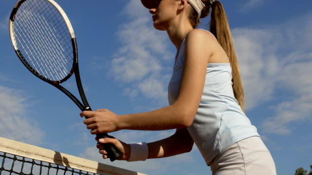 Attractive girl playing tennis on court, beginner practicing shot, slow motion video