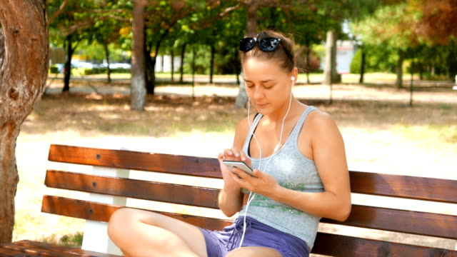 Attractive girl sitting on a bench in the park and listening to music played from her smart phone video