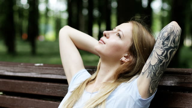 attractive girl with a tattoo on her hand sits on a bench and looks at the sky. - woman portrait forest video stock e b–roll