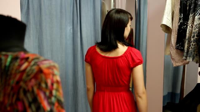 stockvideo's en b-roll-footage met attractive girls looking themselves in a mirror, trying elegant dress. - ridderlijkheid