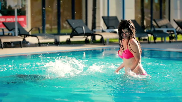 Attractive guy and young woman are having fun in the pool